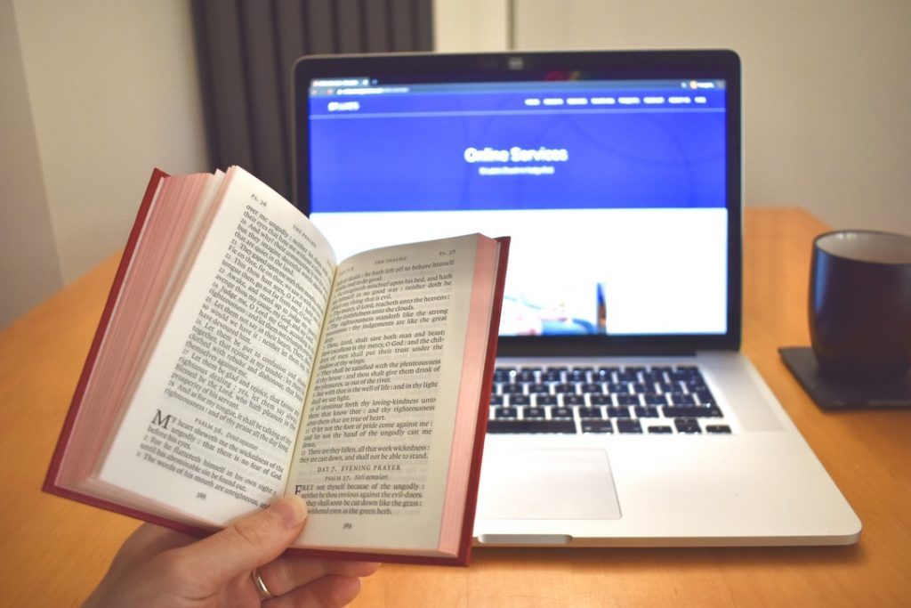 Bible in front of a laptop
